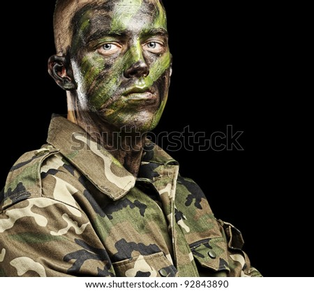 portrait of young soldier with jungle camouflage paint on a black background