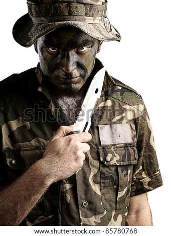 portrait of young soldier with knife and hat against yellow background