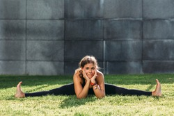 Portrait of young sport woman doing split pose in the park