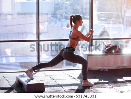 Portrait of young sporty girl doing stretching exercise near large window #631945331