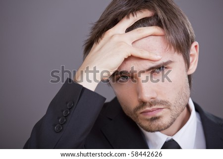 Portrait of young stressed businessman over grey background