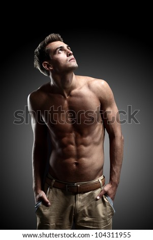 portrait of young strong man against black background