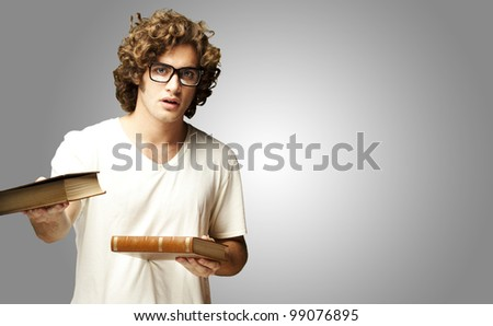 portrait of young student holding books over grey background