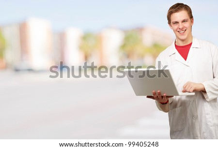 portrait of young student holding laptop against a cityscape