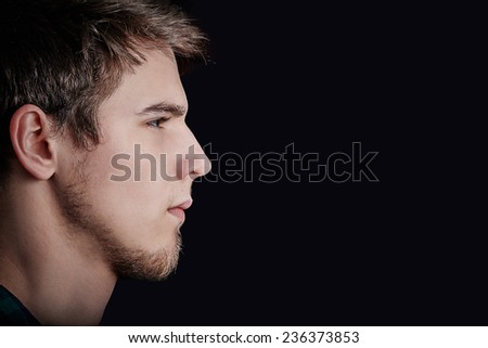 Portrait of young student, man,Head profile portrait side view profile upset,angry,unhappy  isolated black background. Facial expression.