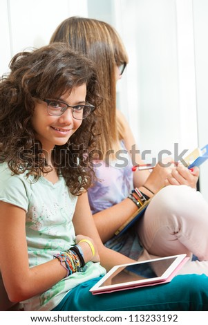 Portrait of young student sitting with digital tablet.