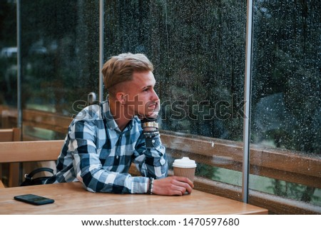 Portrait of young student that sits in cafe at rainy day. One person.