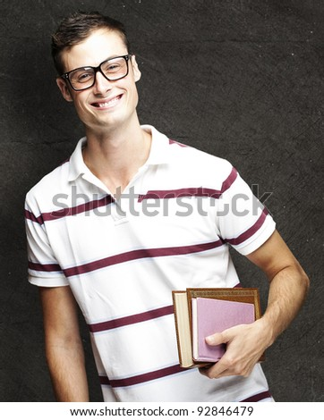 portrait of young student with glasses holding a book against a grunge background