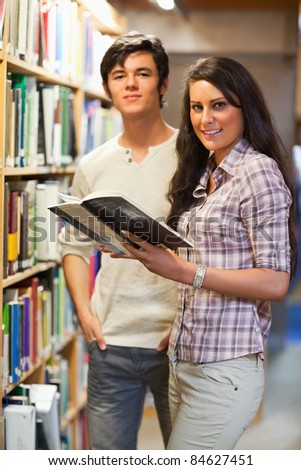 Portrait of young students holding a book in a library