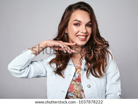 Portrait of young stylish laughing girl model in colorful casual summer clothes with natural makeup isolated on gray background. Looking at camera #1037878222