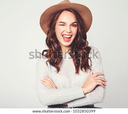 Portrait of young stylish laughing girl model in gray casual summer clothes in brown hat with natural makeup isolated on gray background. Looking at camera and winking #1032850399
