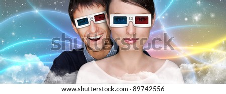 Portrait of young stylish modern couple wearing 3d glasses watching 3d movie against futuristic background  and embracing.