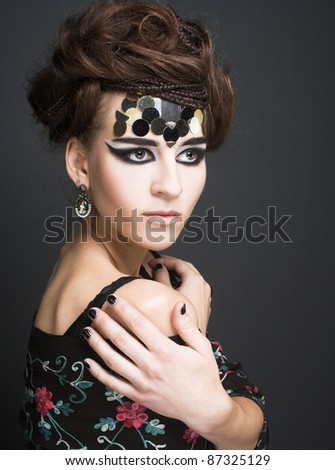 Portrait of young stylish woman with creative visage.