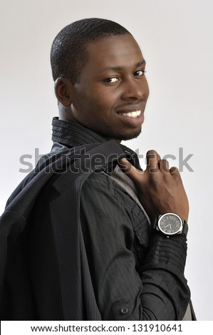 Portrait of young successful fashionable businessman holding jacket over shoulder on grey background