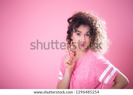 Portrait of young surprised girl with curly hair in loose pink t-shirt shows finger to the side isolated on pink background, place for text, emotion concept #1296485254