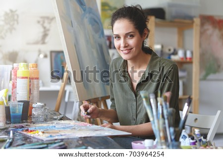 Portrait of young talented female artist making sketches with brightful oils, drawing on easel, having pleasant smile. Smiling painter being busy with her work at workshop. Art, creativeness concept