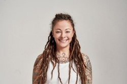 Portrait of young tattooed caucasian woman with dreadlocks wearing white shirt, smiling at camera while posing isolated over grey background. Front view. Horizontal shot
