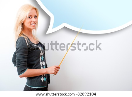Portrait of young teacher pointing on white marker board in modern educational room. Blank balloon with copyspace for your text and logo.