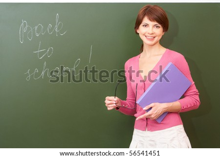 Portrait of young teacher with book and eyeglasses looking at camera by the blackboard