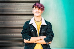 Portrait of young teenager alternative boy and colorful clothes and wall background - urban people and diversity hair coloured concept - youthful and fashion alternative city lifestyle - handsome male
