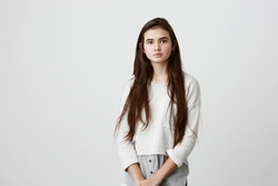 Portrait of young tender brunette girl with long dark hair and healthy skin wearing loose casual clothes looking at camera with calm or pleasant expression. Beauty and youth concept