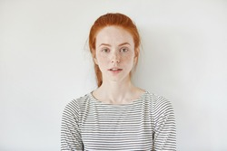 Portrait of young tender redhead teenage girl with healthy freckled skin wearing striped top looking at camera with serious or pensive expression. Caucasian woman model with ginger hair posing indoors