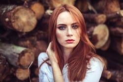 Portrait of young tender redhead young girl with healthy freckled skin wearing white top looking at camera with serious or pensive expression. Caucasian woman model with ginger hair posing outdoors