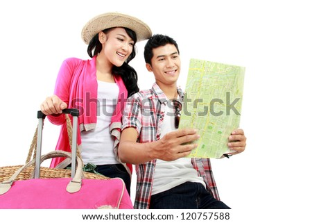 portrait of young tourist with suitcase looking at map