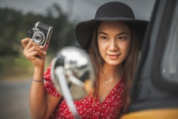 Portrait of young traveler woman hand holding vintage camera and looking classic car side mirror view, Tourist girl on street posing with old car, Happy Asian female on holiday vacation trips