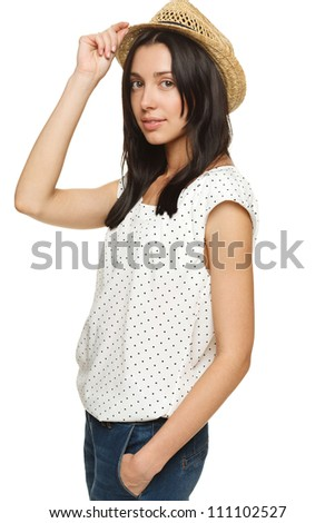 Portrait of young trendy female wearing jeans and straw hat, holding the hat in hand, isolated on white background
