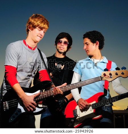 Portrait of young trendy musicians playing electric guitars