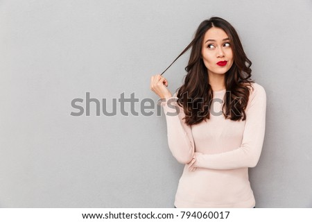 Portrait of young tricky woman touching lock of hair meaning she has something in mind with facial expressions, over gray background