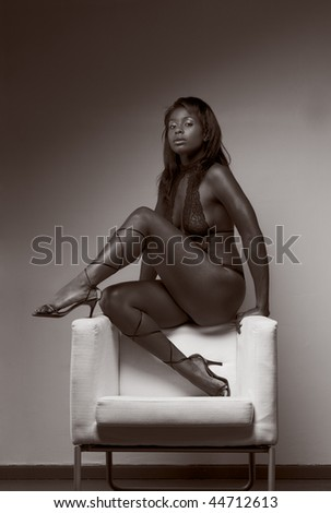 Portrait of young voluptuous sensual Hispanic woman in brown lingerie sitting on top of armchair