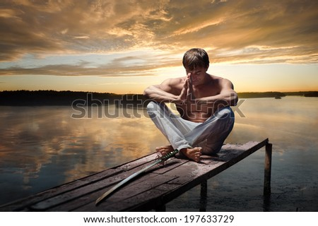 Portrait of young warrior with Japanese sword on sunset background