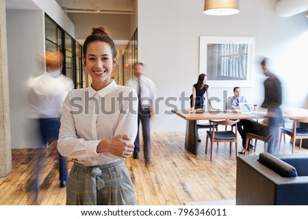 Portrait of young white woman in a busy modern workplace