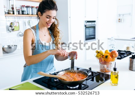 Portrait of young woman adding pepper and mixing food in frying pan.