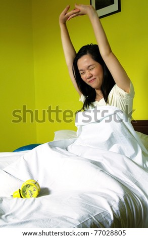 portrait of young woman and alarm clock in bedroom