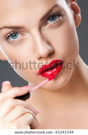 Portrait of young woman applying lip gloss