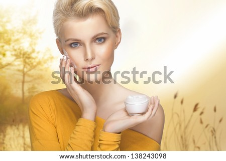 Portrait of young woman applying moisturizer cream on her pretty face