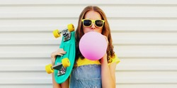 Portrait of young woman blowing bubble gum or balloon with green skateboard on a white background