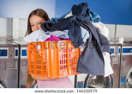 Portrait of young woman carrying basket full of dirty clothes in laundry