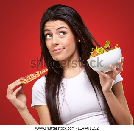 portrait of young woman choosing pizza or salad against a red background