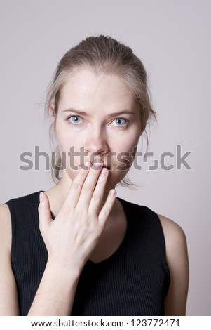 portrait of young woman covering her mouth with hand