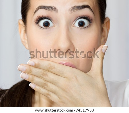 Portrait of young woman covering her mouth with hand looking shocked.