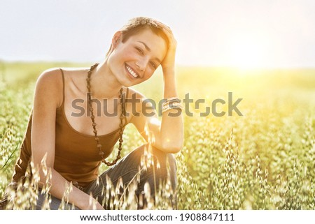 Portrait of young woman crouching in field of grass Сток-фото ©