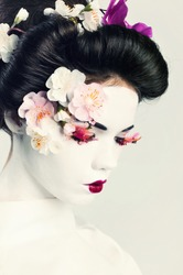 Portrait of young woman decorated in japanese style. Geisha girl
