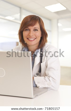 Portrait of young woman doctor in white coat at computer