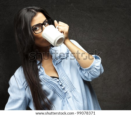portrait of young woman drinking coffee against a grunge wall