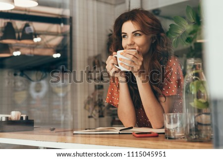 portrait of young woman drinking coffee at table with notebook in cafe