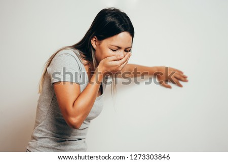 Portrait of young woman drunk or sick vomiting over gray background #1273303846